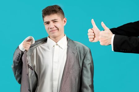The teenager feels uncomfortable in the clothes of an adult man, but hands on the side approve with a gesture thumbs up