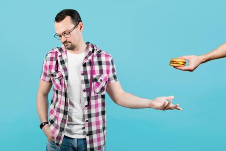 the guy reluctantly agrees to take burger and turns away from the person who offers him food