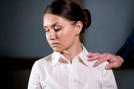 woman rejects the fact that a man touches her shoulder, turns away from this gesture