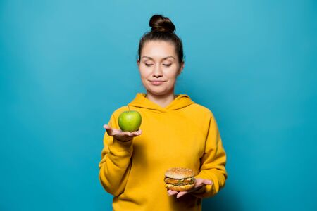 a nice girl is going to give preference to an apple which holds on one hand, in the other hand she still has a burger Standard-Bild