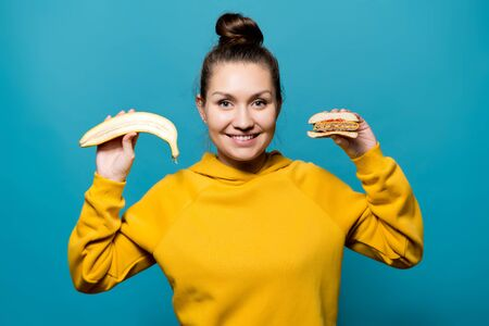 smiling girl in a bright sweatshirt shows cuts of a banana and a burger close up