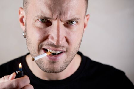 unshaven handsome man is about to light a cigarette and looks with a claim at the camera, close up