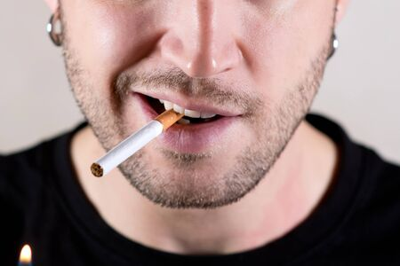 lower half of the face of an unshaven pierced man who is about to light a cigarette