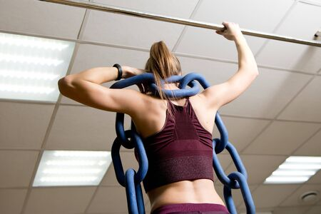 sports girl with a weighting chain on her shoulders prepares for pull-ups, back view, no face Imagens