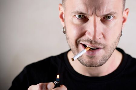 brutal green-eyed pierced man with a stern face is about to light a cigarette, holding a lit lighter in front of him, close up