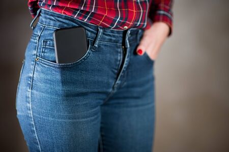 close-up of a phone in a black case that sticks out of a girl's jeans pocket