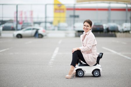 young woman with glasses in a supermarket parking lot sitting on a children's plastic car