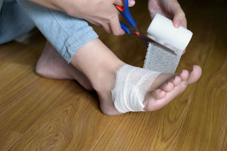A woman is bandaging her injured leg. Close-up. The girl injured her leg at home and applies the bandage herself