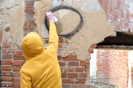 A teenager draws on a wall of an abandoned building a spray can of paint. View from the back Stock fotó