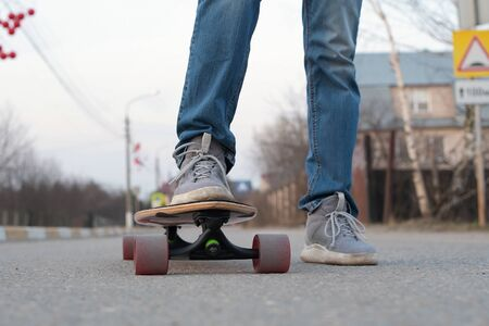 teenager very close to camera on a skateboard, close-up of legs