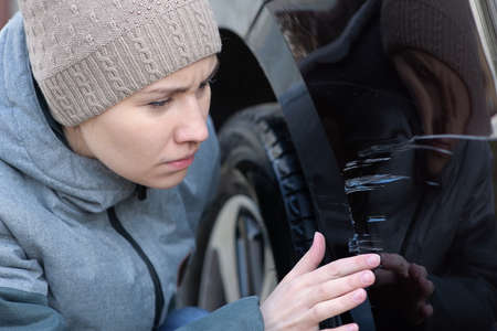 Young woman sadly examines fresh scratches on the bumper of her car, close up