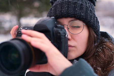 On a snowy day, a girl photographer takes pictures of the winter forest. Strong bokeh
