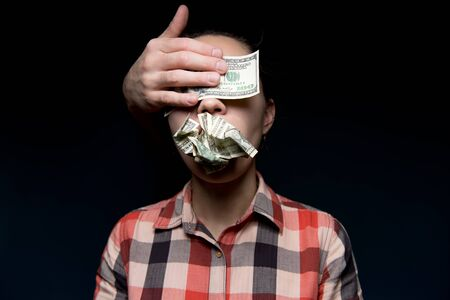 Crumpled dollars are in the woman s mouth, her eyes are closed by a stranger s hand and a hundred-dollar bill. Money made the woman close her eyes and be silent. Corruption, blackmail