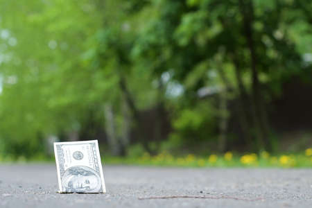 One hundred dollar bill lies on the pavement. Lost money in the park