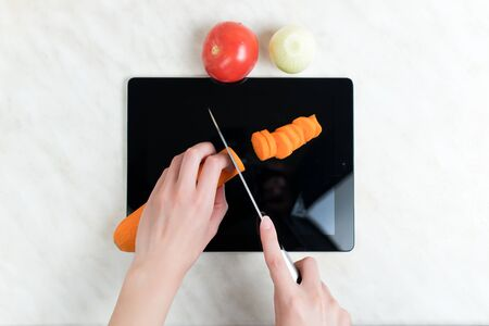 A woman cuts vegetables with a knife on an old graphics tablet, which serves as a cutting board. Top view 版權商用圖片