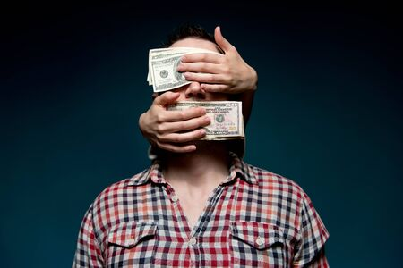 Hands from the dark cover the eyes and mouth of a working man with dollars. Guy blinded by money