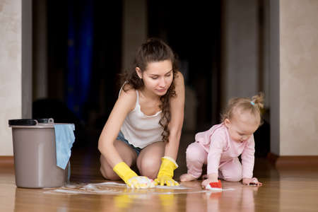 Mom and little daughter wash the floor together at home Stock fotó