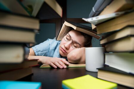 A young student girl fell asleep on a book hiding behind another book. Tired student preparing for exams at the institute