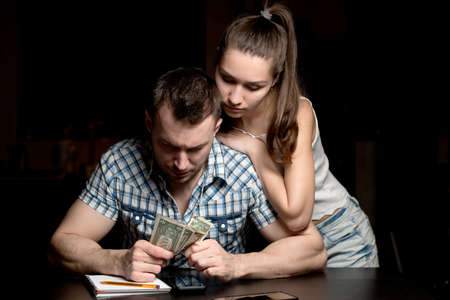 A young woman supports a man who counts the rest of the money at a difficult time, when the family hardly survives. The financial crisis in a young family