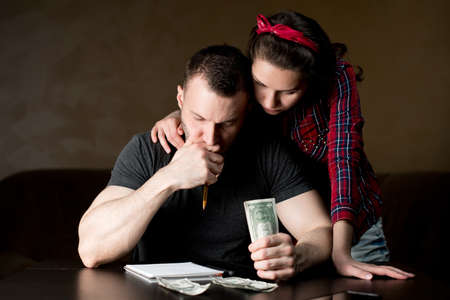 Husband and wife calculate family budget. The husband seriously considers and holds money, the wife supports him Stock fotó