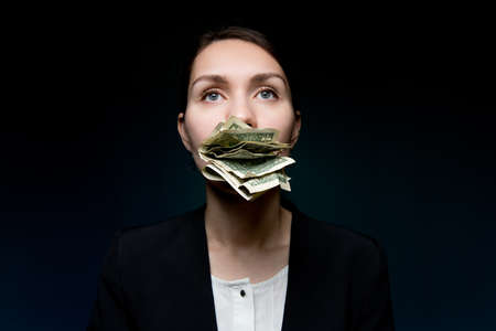 Small money in the mouth of a business woman, she is silent because of small money and looks into the void. Dark background