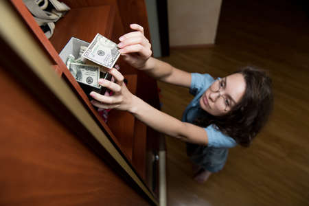 A girl puts or takes dollars from a money-box on the top shelf of a closet. Crisis. Selective focus on the piggy bank, top view.