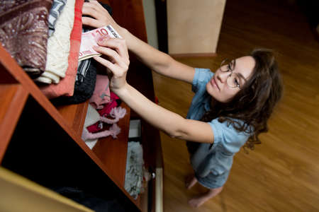 Girl hides a small stack of euro banknotes in clothes in a wardrobe. Young woman makes reserves for hard time