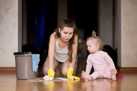 A disgruntled mother launders the floor with her hands while her little daughter sits nearby. The difficulties of motherhood