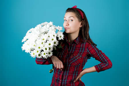 Country girl with a bouquet of white chrysanthemums on a blue background. Girl holds flowers under her arm and smiles coquettishly Stock fotó