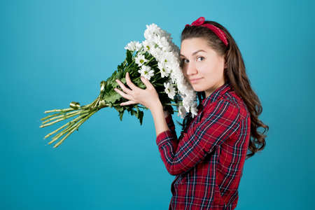 a country girl in a red shirt on a blue background presses a large bouquet of white chrysanthemums to her cheek Stock fotó