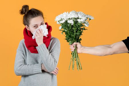 Allergic girl and a bouquet of flowers - white chrysanthemums on yellow background