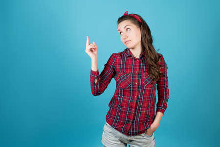 A country girl in a red plaid shirt looks coldly to the side and shows her middle finger. Isolated on blue background.