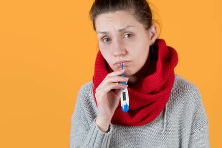 a cold girl in a sweater and scarf holds an electronic thermometer in her mouth on yellow background
