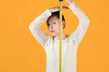 girl measures her height, holding a measuring tape nearby and looks at the camera, isolated on orange-yellow