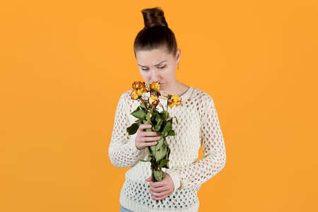 girl sadly looks at a bouquet of wilted flowers that she holds in her hands. isolated on orange-yellow Stock fotó