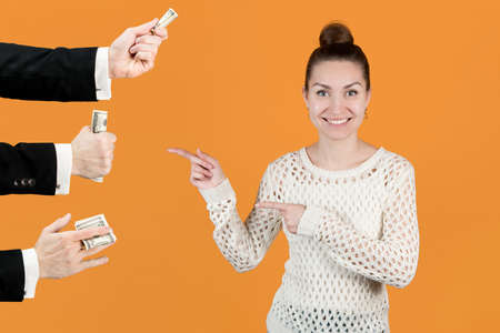 The girl joyfully points to the men's hands that hold out her money. Isolated on a yellow background. Sponsors girls, wealthy boyfriends Stock fotó
