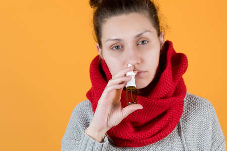 A young woman in a red scarf of a sickly look sprays a cure for colds and flu in her nose. Isolated on orange background.