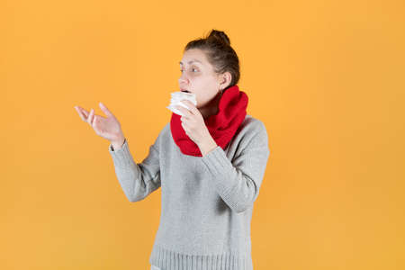 a sickly-looking girl in a scarf and sweater holds a napkin near her nose and reaches out to the side, turning to someone. Isolated on orange yellow background.