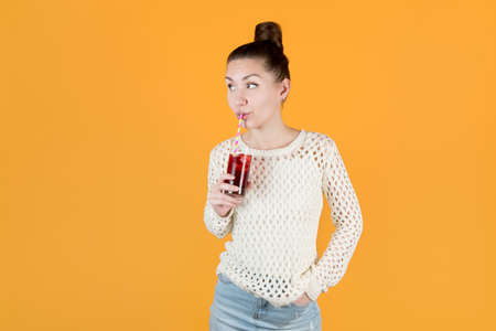 girl drinks juice through a straw and looks away. isolated on orange-yellow Stock fotó