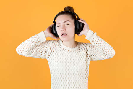 girl enthusiastically listens to music in large headphones, closing her eyes. isolated on orange-yellow