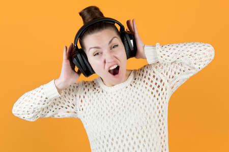 girl screaming holding big headphones on her head, isolated on orange-yellow