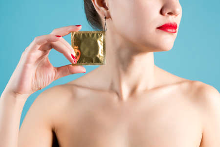 A young girl holds a condom in her hand with red nails and red lipstick. Blue background Stock fotó