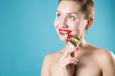 Girl playfully holds the edge of the wrapper of a red condom with her teeth, smiling. The girl has red lipstick and nails. Blue background, girl without clothes