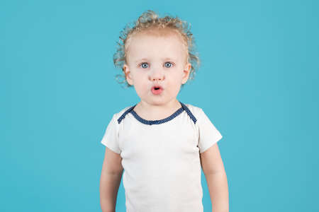 Cute curly baby girl of two years raises folds her lips in a straw on a blue background. Isolated on blue