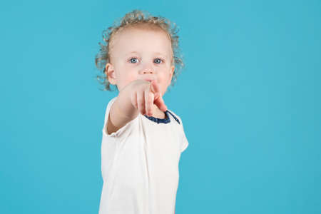 Two-year-old curly baby girl pokes a finger at the viewer. Child shows on camera. Isolated on blue Stock fotó