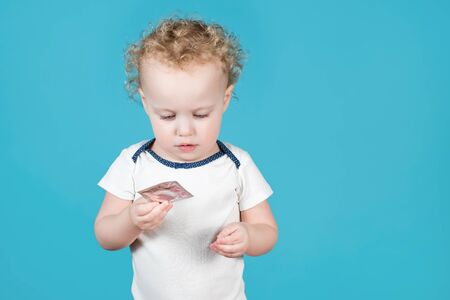 Two-year-old curly baby girl holds a condom in her hand. Isolated on blue