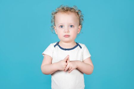 Two-year-old curly baby girl carefully looks at the camera, hands clasped together. Isolated on blue
