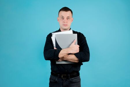 A tired office employee in a black shirt and folders with documents in his hands looks into the void. Isolated on blue