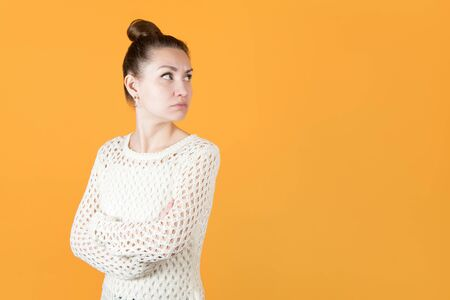 girl with resentment looks at someone over her shoulder, hands clasped on her chest. Isolated on orange-yellow background Stock fotó