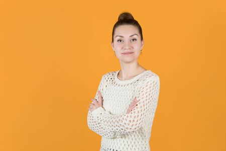 the girl folded her arms and proudly looks straight. Isolated on orange-yellow background